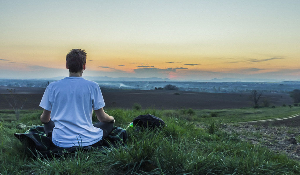Photo of a person sitting on a grassy landscape, facing the sunset and meditating
