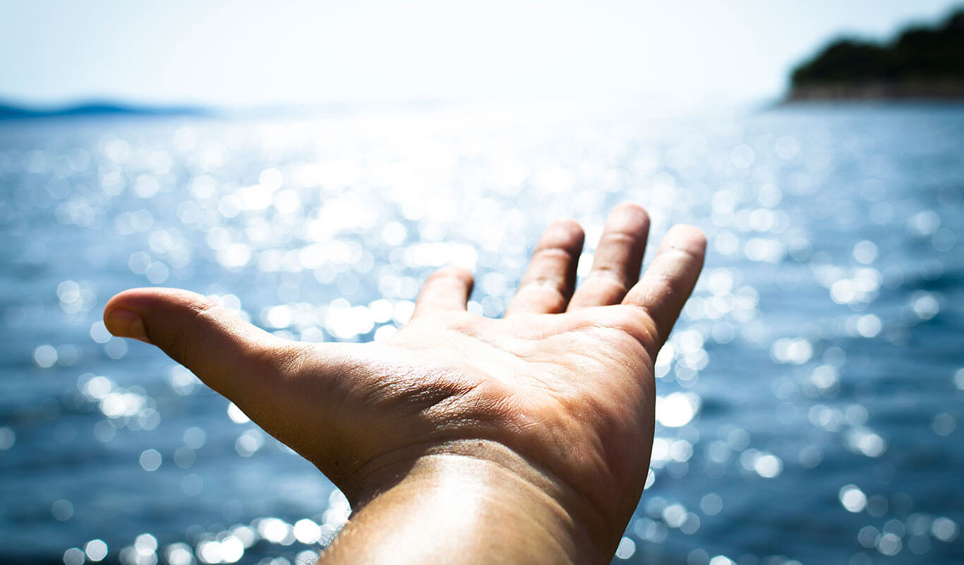 Photo of an outstretched hand against a large body of water